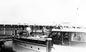 "Courier in the ""place of things to come:"" the West Palm Beach Municipal Marina, during Christmas 1948. Courier took a long cruise from Chicago nearly all the way to the end of the United States, a long cruise in a yacht then and now. In the background is the Flagler Bridge, the northernmost bridge from the mainland to the Town of Palm Beach. Fairly new when the photograph was taken, it has been replaced by a new bridge. Chet and his wife Myrtle would move to Palm Beach in 1957, where they would live the last years of their lives."