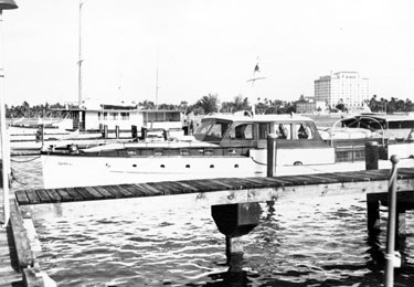 """Courier in the """"place of things to come:"""" the West Palm Beach Municipal Marina, during Christmas 1948. Courier took a long cruise from Chicago nearly all the way to the end of the United States, a long cruise in a yacht then and now. More of Palm Beach is in the background. Chet and his wife Myrtle would move to Palm Beach in 1957, where they would live the last years of their lives."""