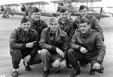 A group at the Cal-Aero Academy, 1 April 1942. Left to right: W.H. Wamsley, IA; D.G. Shofner, AR; R.A. Litwiller, NE; H.J. Schmidt, KS; D.B. Thomas, CA; S.R. Swartout, CA. Behind them are Stearman PT-13 training aircraft.