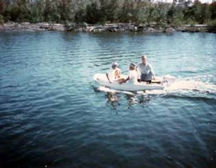 """Slightly overloaded: on our last yacht, we had two dinghys. The smaller of the two is shown at the left. Called a """"Dilly Boat,"""" it was an 8′ long, cathedral hull fibreglass boat, not really suitable for all of the three people occupying it in this photo, taken at the Ocean Reef Resort on Key Largo. One of the things that has changed dramatically since our years on the water is the engine horsepower that propel ships of all sizes in the water. For me, it's still hard to believe the power that's put into boats now, large and small, and the speeds they routinely achieve. However, this craft took slow to a new level. The outboard motor driving this small craft was only a 3 hp Johnson with a self-contained fuel tank."""