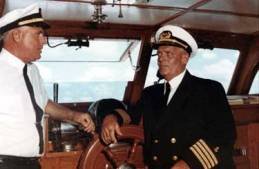 """A fine crew: the larger the yacht, the larger the crew; our last one usually required two. Elmer """"Bud"""" Curless (left) and Captain James North pose in their dress uniforms. True to form, we had khaki ones for normal duty. It's fair to say that many people who go into yachting do so to create their own """"navy"""" (or in our case our own coast guard.) Such a pose gives an HMS Pinafore aspect to the whole thing, with one notable exception: both the crew and their employer were not shy about using a """"big, big D."""" (Photo by Bernice Ransom Studios)"""